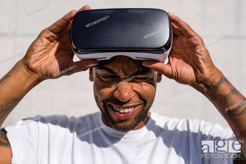 Stock Photo: Man putting on Virtual Reality Glasses.
