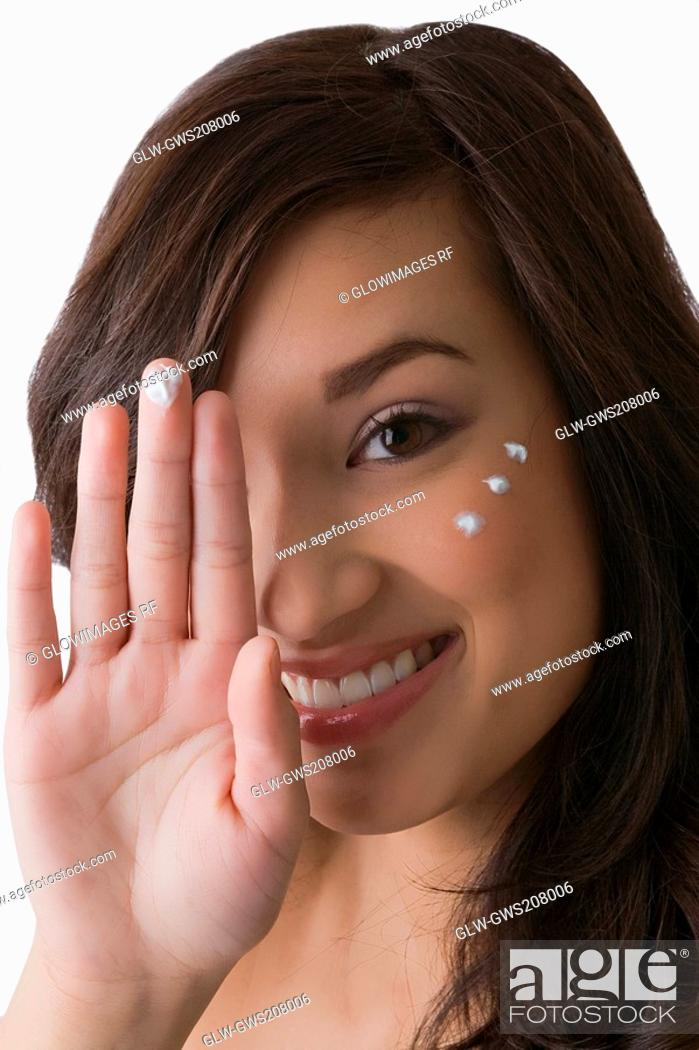 Stock Photo: Portrait of a young woman showing cream on her fingertip and smiling.
