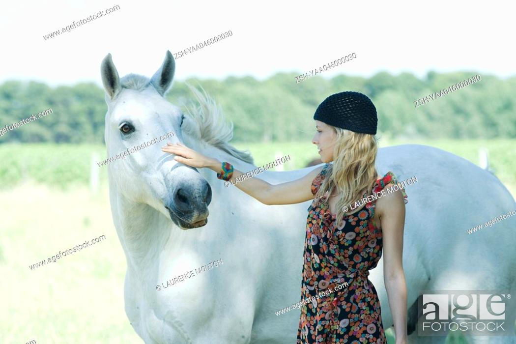 Stock Photo: Young woman petting horse.