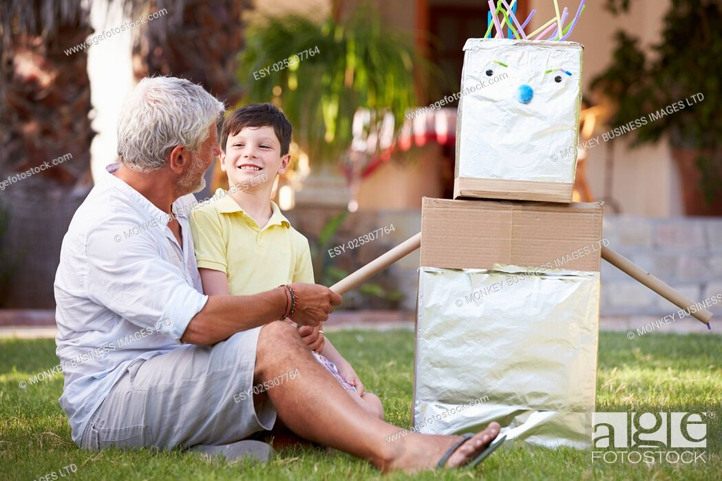 Stock Photo: Grandfather And Grandson Building Model Robot In Garden.