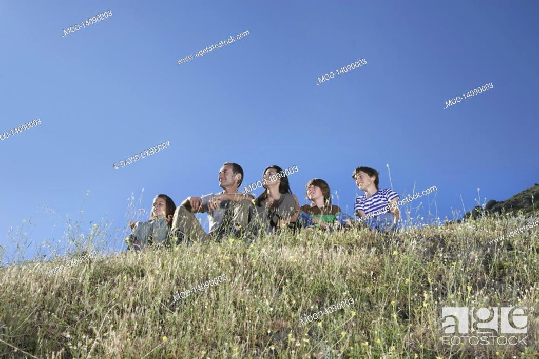 Stock Photo: Parents with three children 7-12 sitting on hill looking at view.