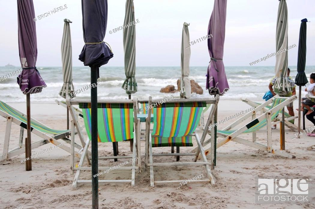 Stock Photo: Closed Umbrellas on a emty Beach.