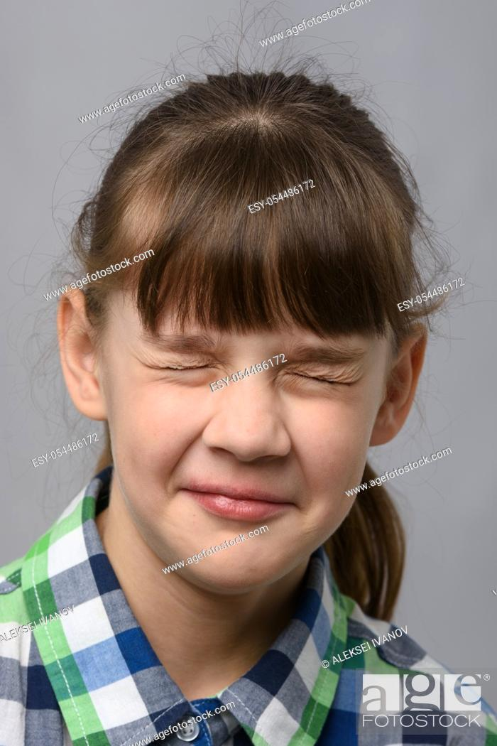 Stock Photo: Portrait of a ten-year-old girl who closed her eyes, European appearance, close-up.