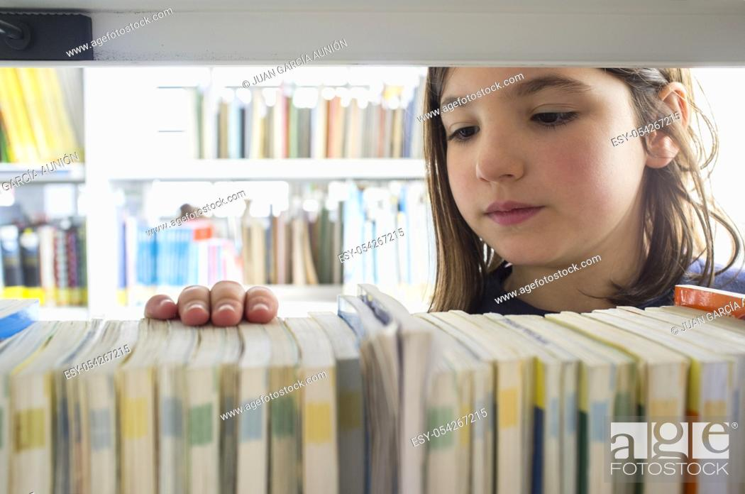 Stock Photo: Young girl selecting books from library bookshelf. Children creativity and imagination concept.
