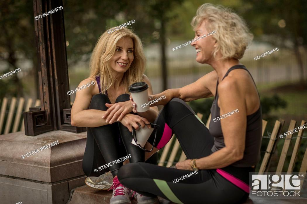 Photo de stock: Two mature female friends training in park, sitting on wall with takeaway coffee.