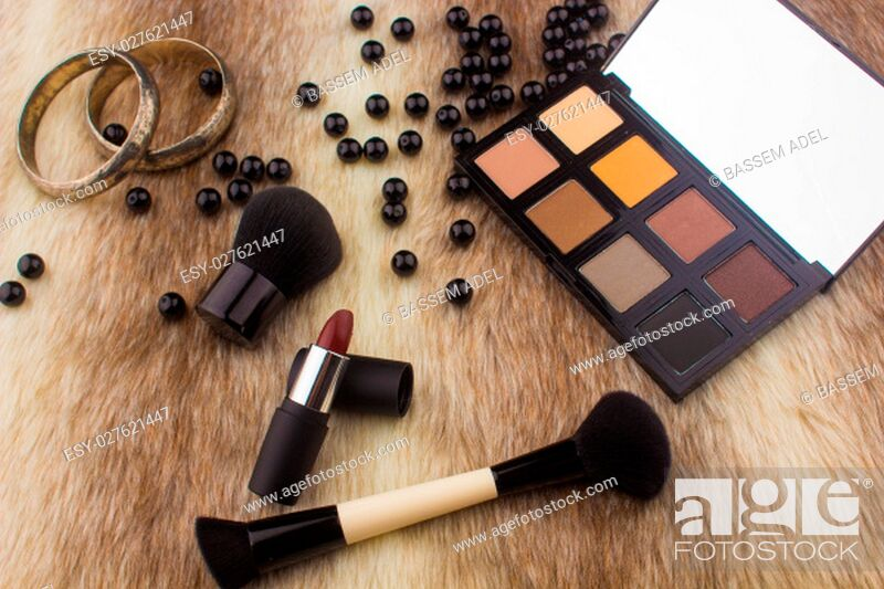 Photo de stock: Makeup tools on Fur background / featuring eyeshadow palette, lipstick, makeup brushes on a fury background.