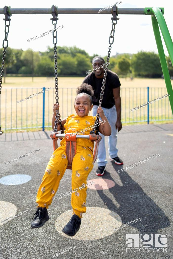 Stock Photo: Father with happy daughter swinging on a playground.