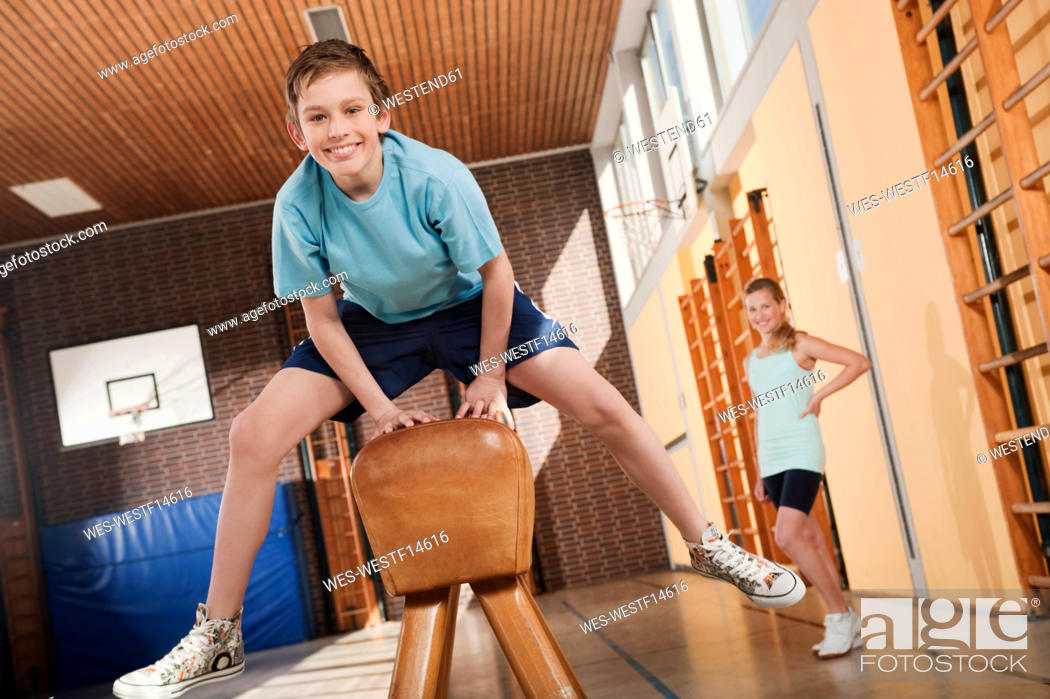 Stock Photo: Germany, Emmering, Boy 12-13 jumping with girl standing in background.