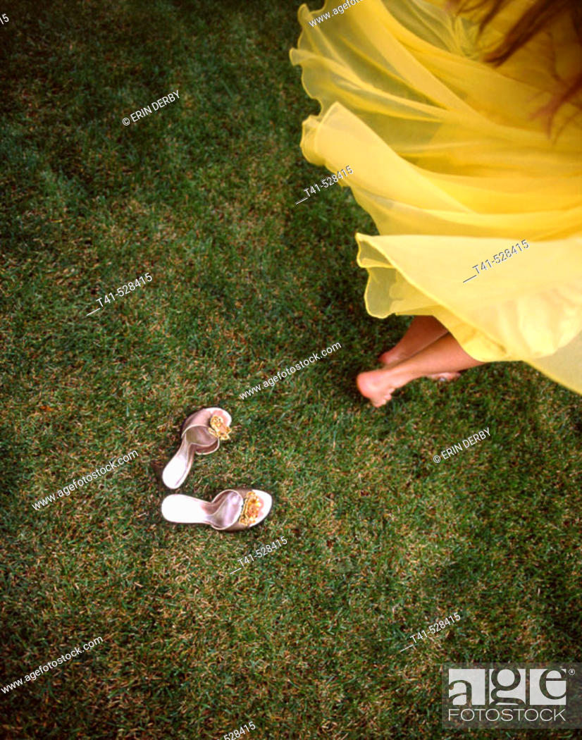 Stock Photo: A woman spinning in a vintage yellow dress with her mother's vintage shoes left behind.