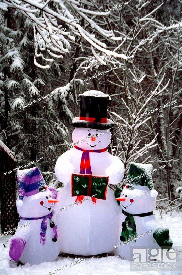 Stock Photo: An inflatable snowman and snow kids outside a home during the winter Christmas season.