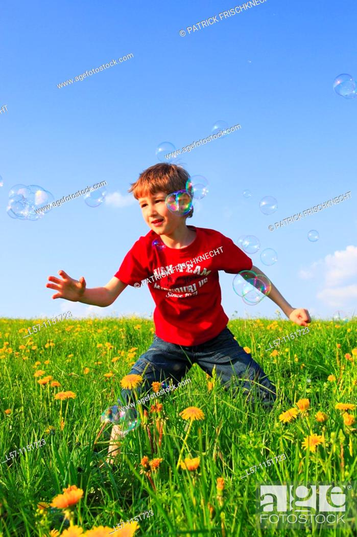Stock Photo: boy playing with bubbles in field of Dandelions, Zuercher Oberland, Zuerich, Switzerland.