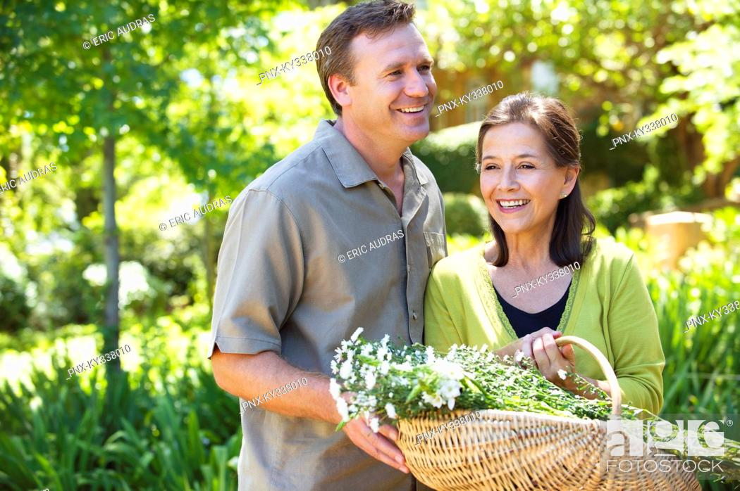 Stock Photo: Man with his mother holding basket of flowers outdoors.