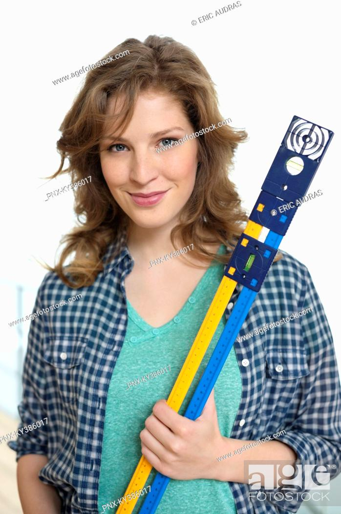 Stock Photo: Portrait of a woman holding a level.