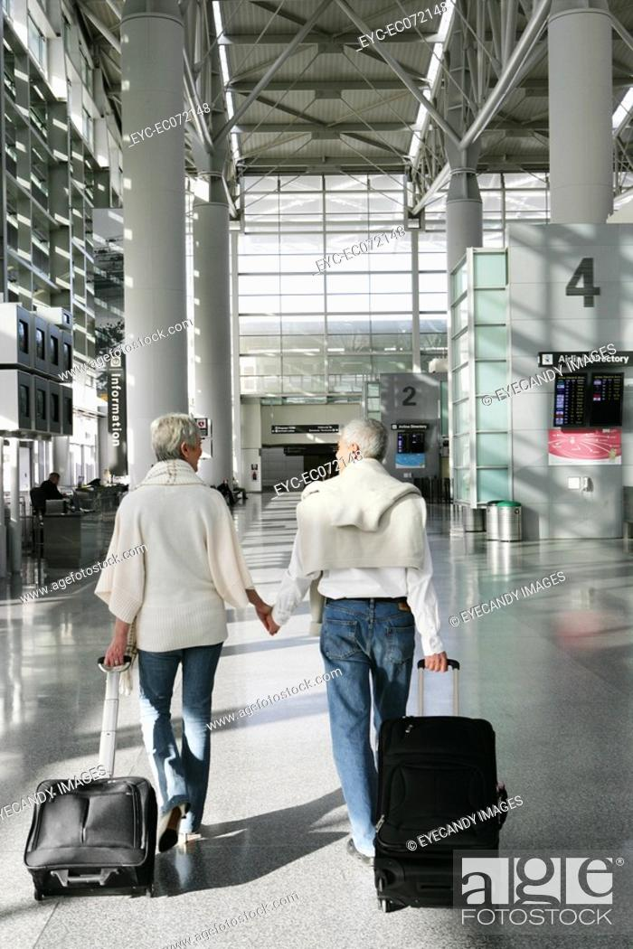 Stock Photo: Mature couple walking in airport.