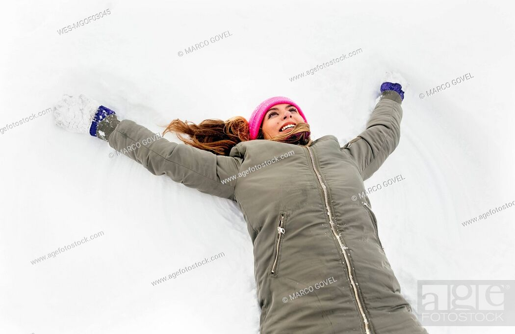 Stock Photo: Young woman making a snow angel.