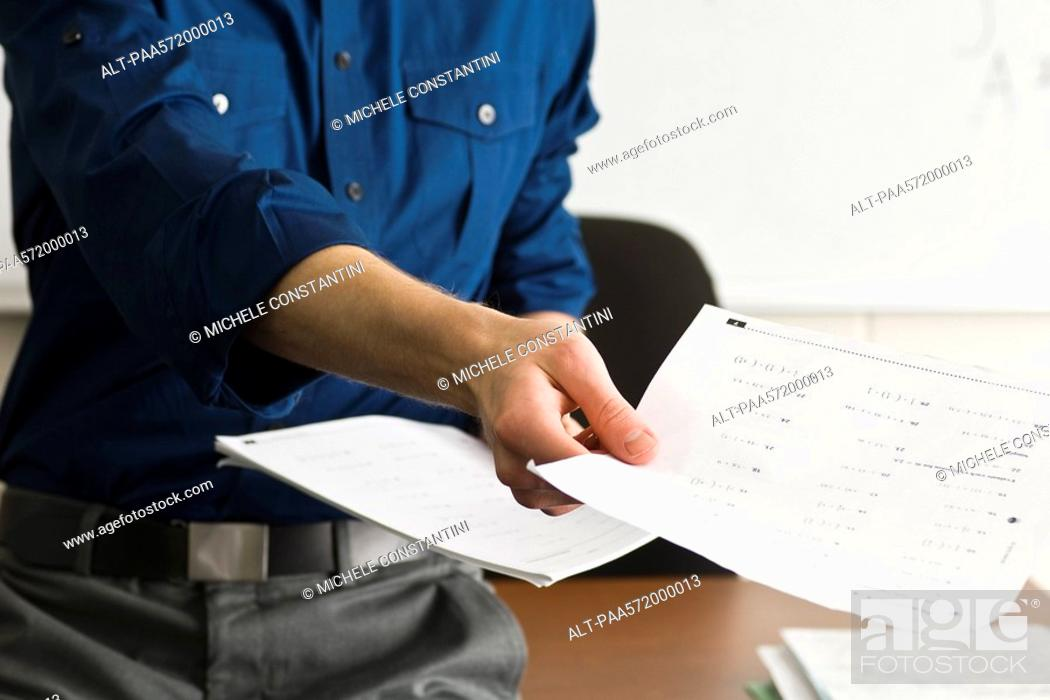 Stock Photo: Teacher handing out classwork assignment.