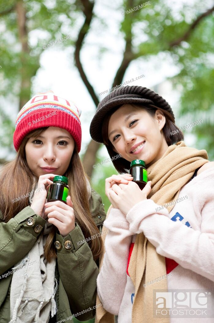 Imagen: Young women holding drink and smiling at the camera together.