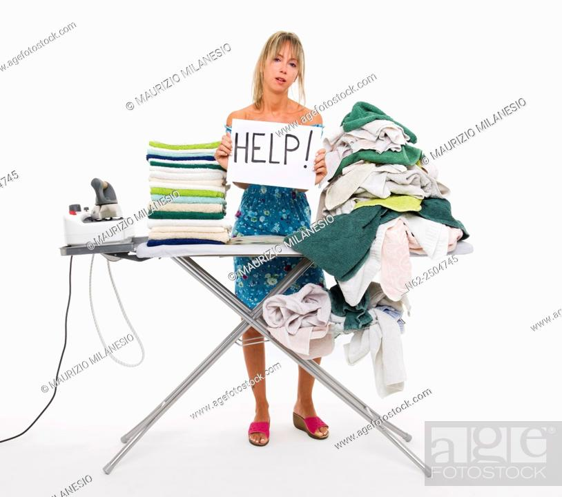 Stock Photo: Woman behind a board covered with clothes to be ironed, exposes a sign reading aid.