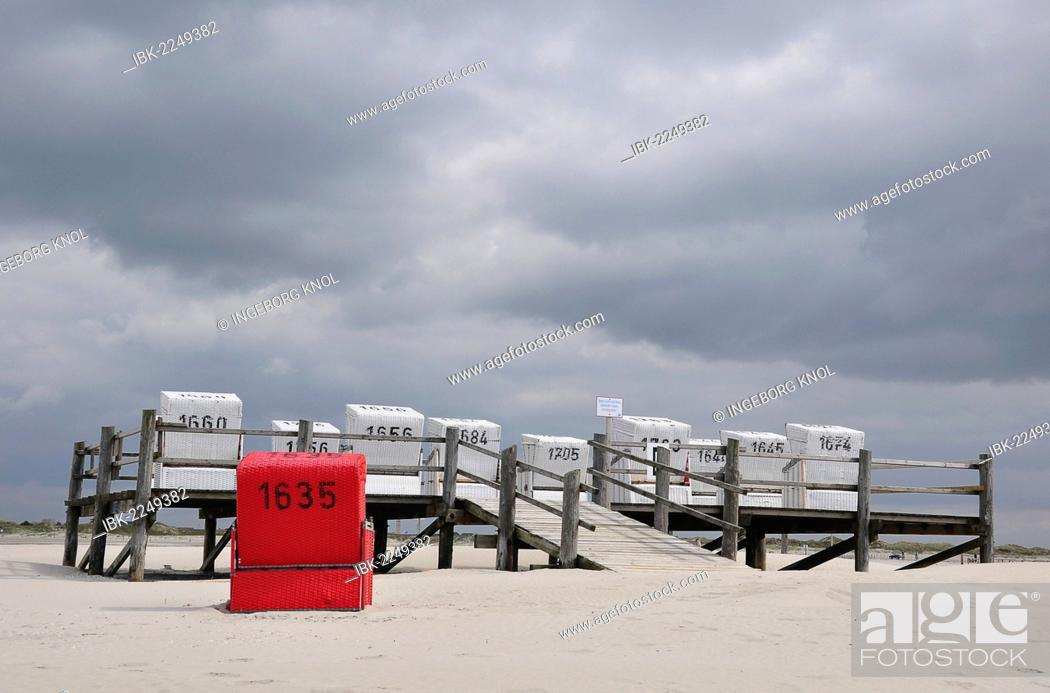 Imagen: Roofed wicker beach chairs on a platform on stilts, beach on the North Sea, St. Peter-Ording, Schleswig-Holstein, Germany, Europe.