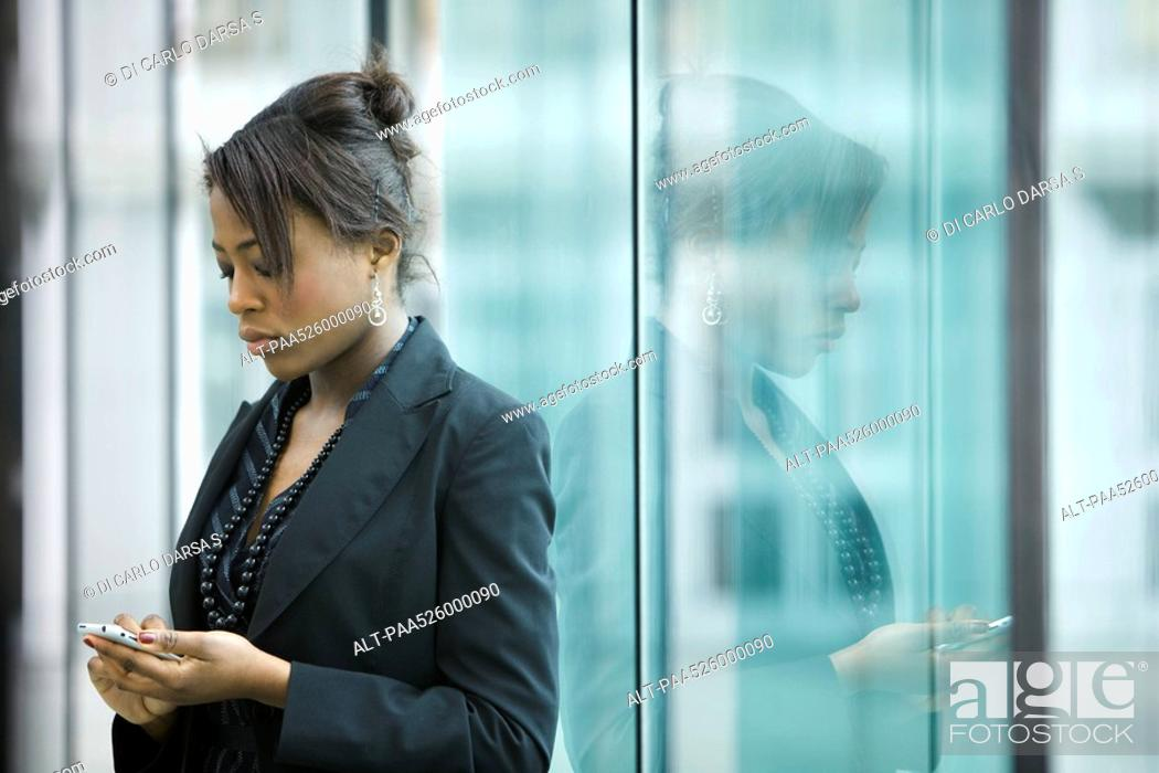 Stock Photo: Businesswoman using cell phone, looking down.