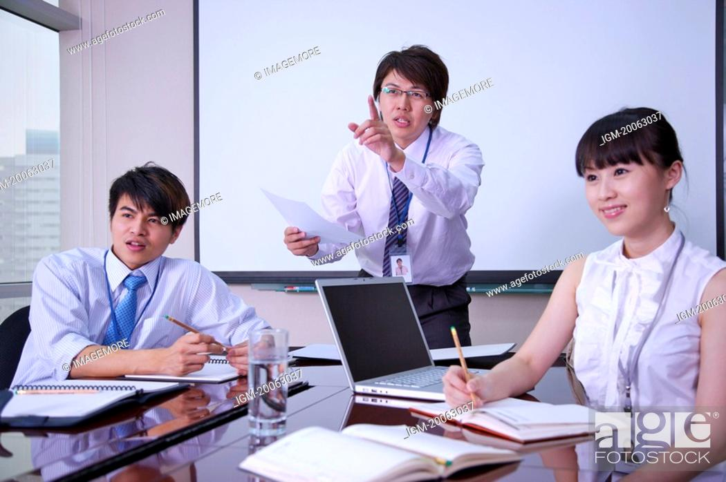 Stock Photo: Three colleagues working in office and looking away with smile.