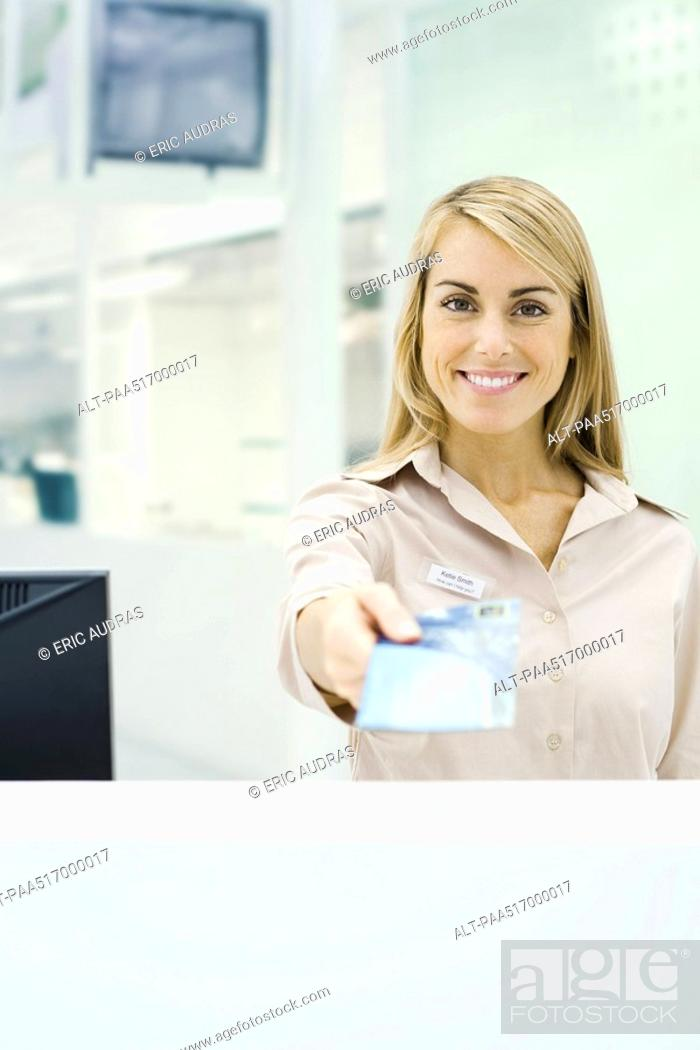 Stock Photo: Travel agent holding out ticket, smiling at camera, personal perspective.