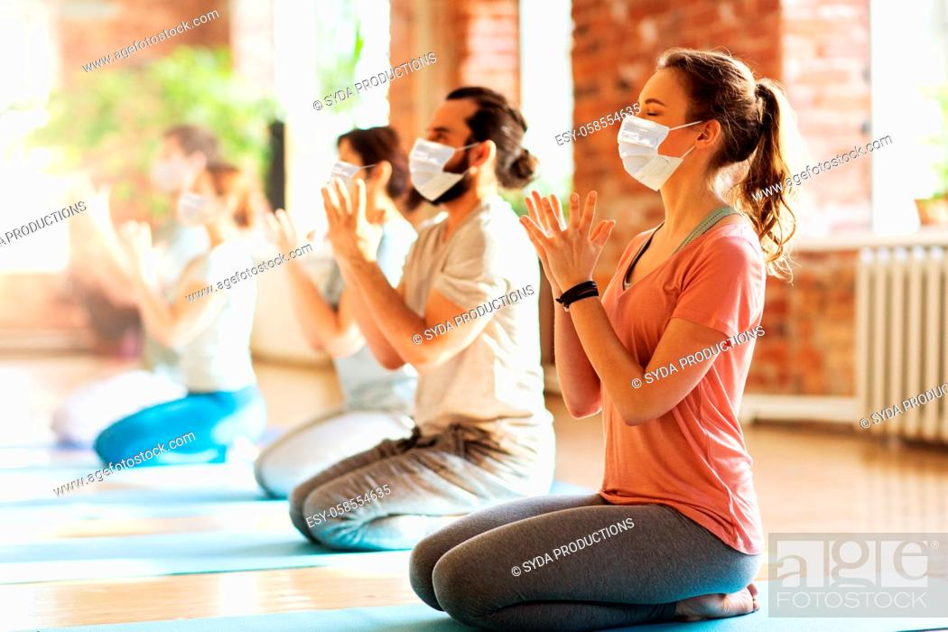Stock Photo: group of people in masks meditating at yoga studio.