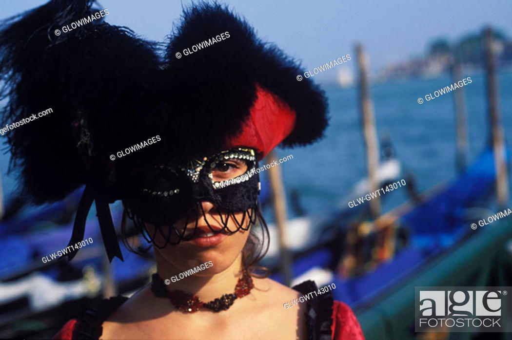 Stock Photo: Portrait of a young woman wearing carnival mask, Venice, Veneto, Italy.
