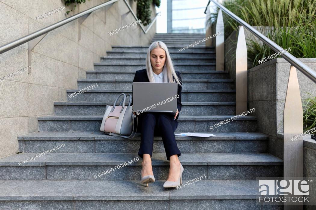 Stock Photo: Young businesswoman sitting on stairs in the city using laptop.