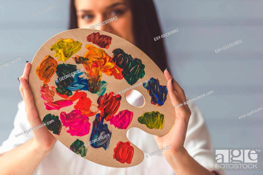 Imagen: Attractive young female artist is holding a color palette, looking at camera and smiling while standing in her studio.