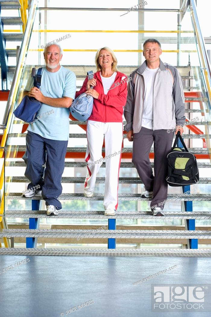 Stock Photo: Two senior men and woman with gym bags walking down steps, smiling, portrait.