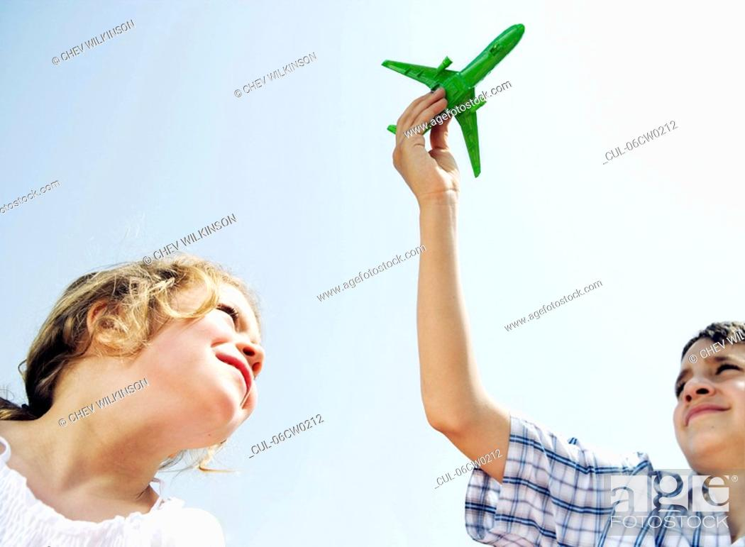 Stock Photo: Boy and girl looking up at toy plane.