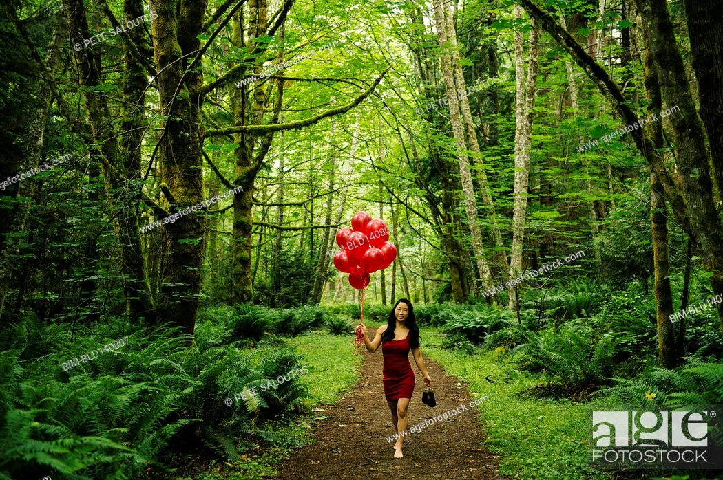Stock Photo: Korean woman holding red balloons in lush forest.