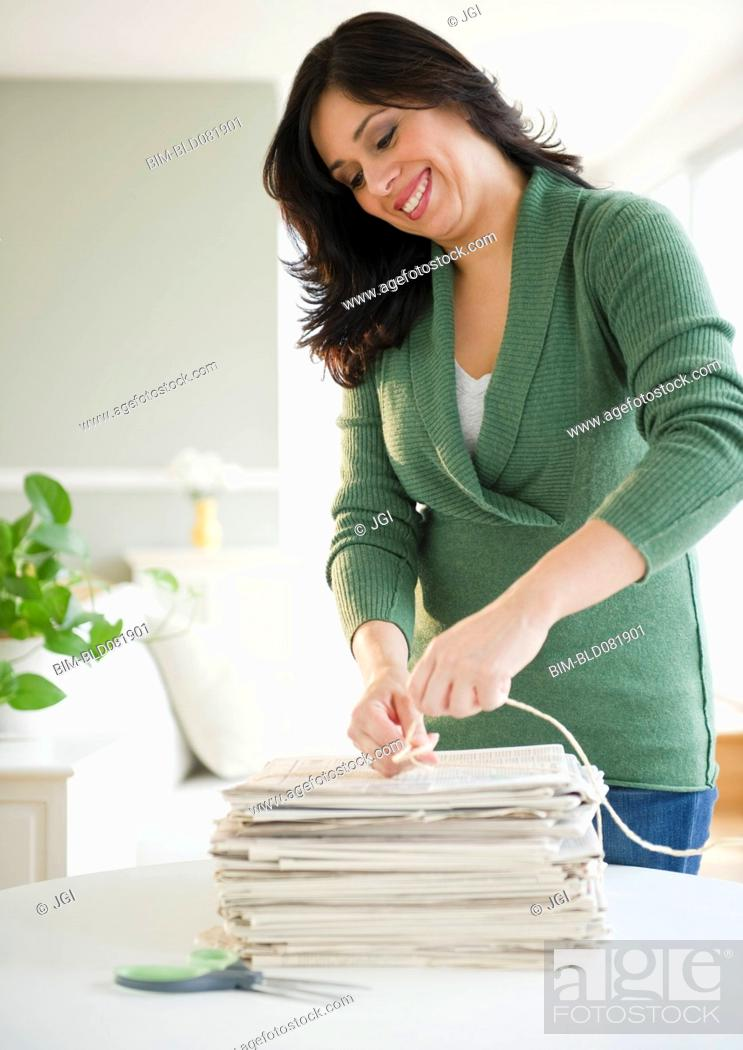 Stock Photo: Smiling Hispanic woman trying newspapers in bundle.