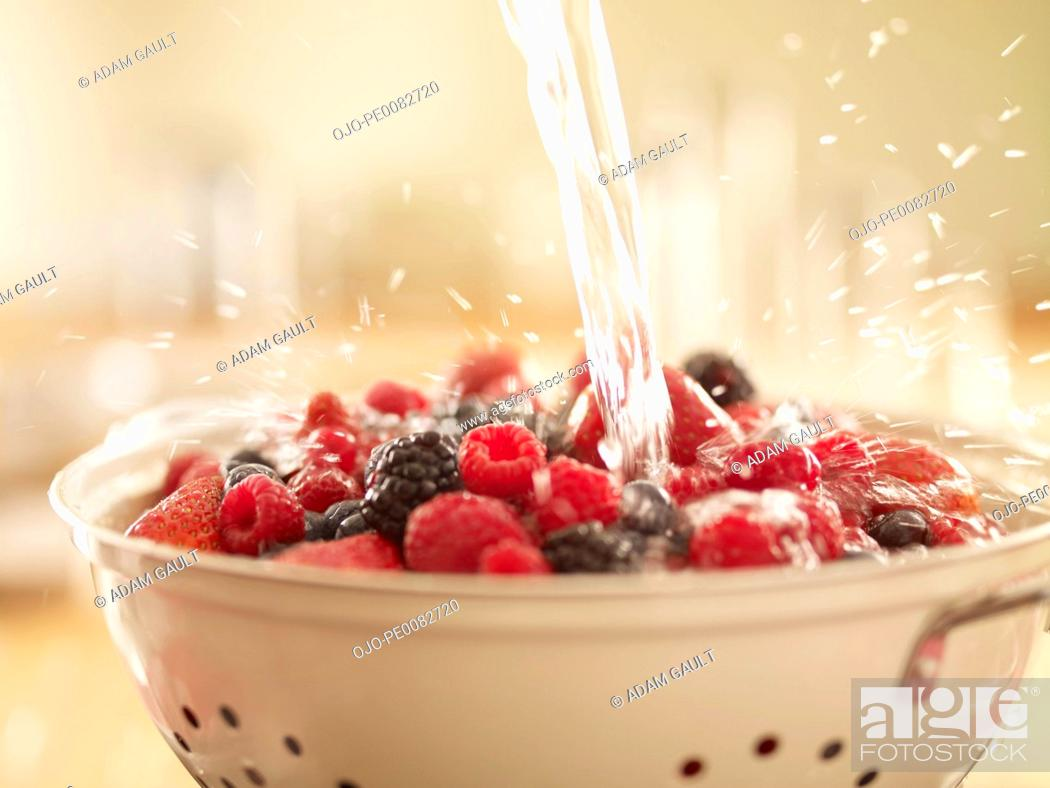 Stock Photo: Water splashing over berries in colander.