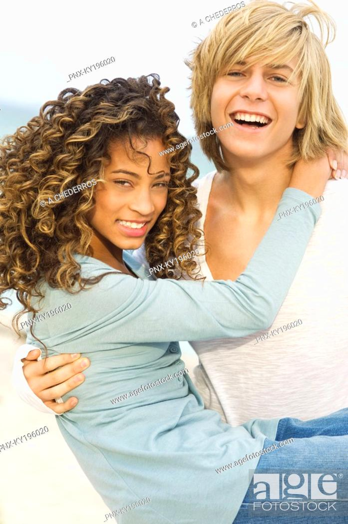 Stock Photo: Teenage boy carrying a girl on the beach.
