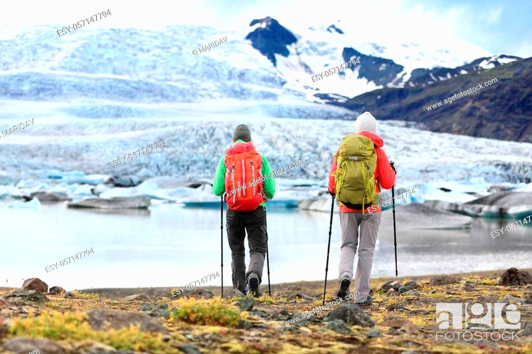 Stock Photo: Hikers - people on adventure travel on Iceland. Hiking man man woman walking to glacier and glacial lagoon / lake of Fjallsarlon, Vatna glacier.