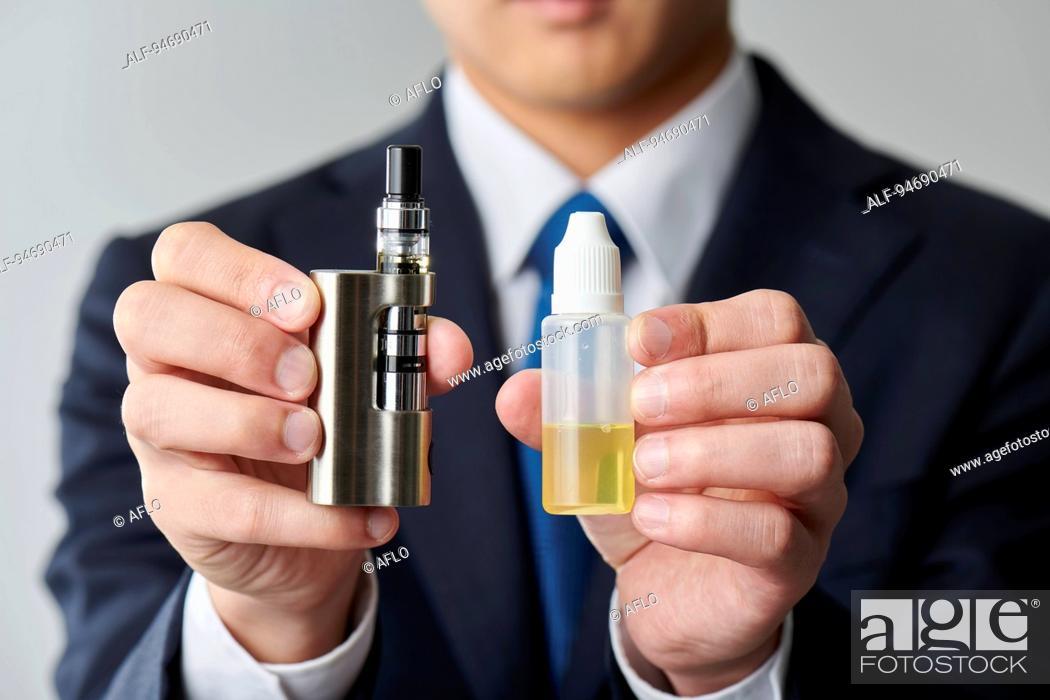 Stock Photo: Young Japanese man smoking electronic cigarette.