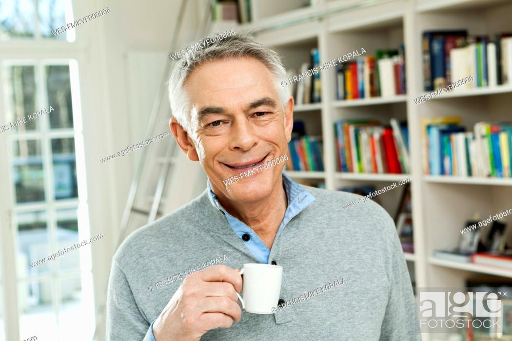 Stock Photo: Germany, Berlin, Senior man with coffee cup, smiling, portrait.