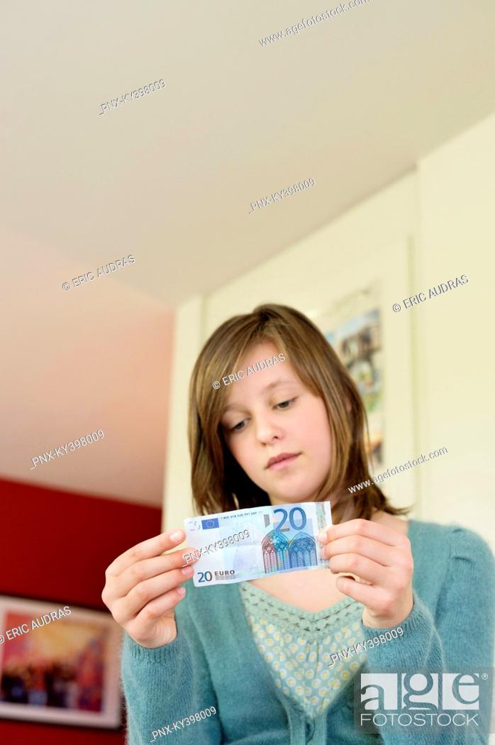 Stock Photo: Girl holding pocket money at home.