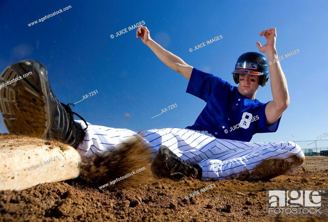Stock Photo: Baseball player, in blue uniform, sliding safely into base on pitch during competitive game surface level, blurred motion.