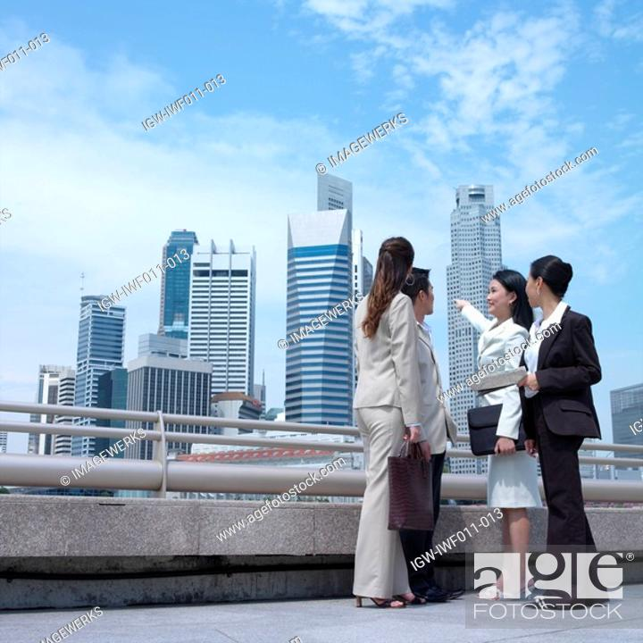 Stock Photo: Low angle view of a businesswoman pointing towards buildings.
