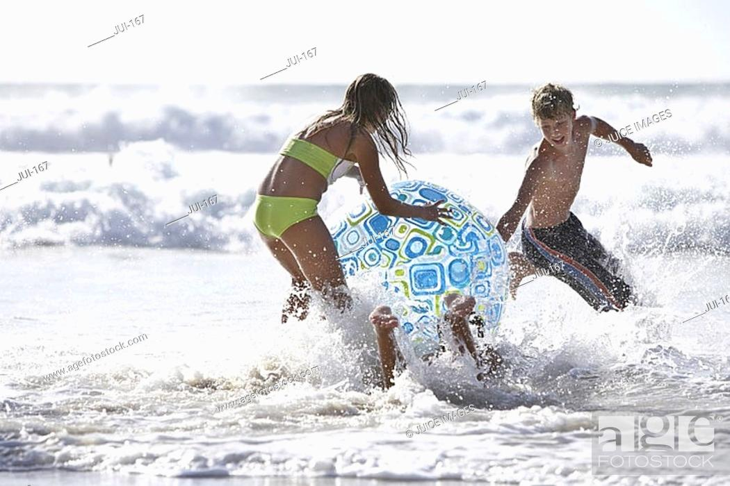 Stock Photo: Three teenagers 13-15 playing with large inflatable beach ball in surf, laughing.