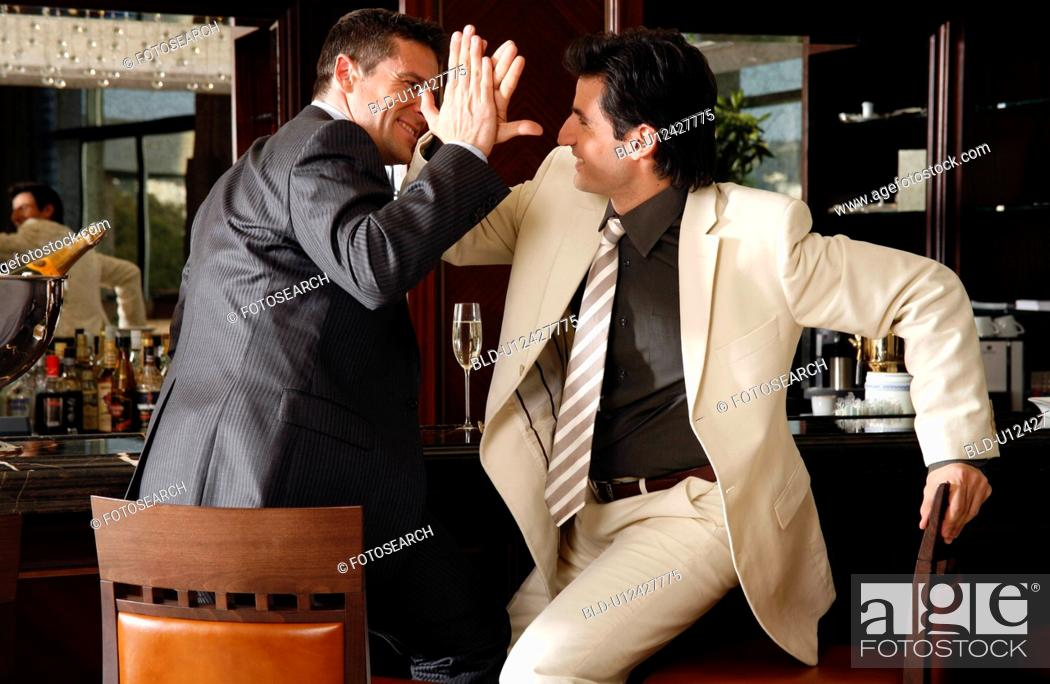 Stock Photo: Two men slapping hands in agreement at a bar.