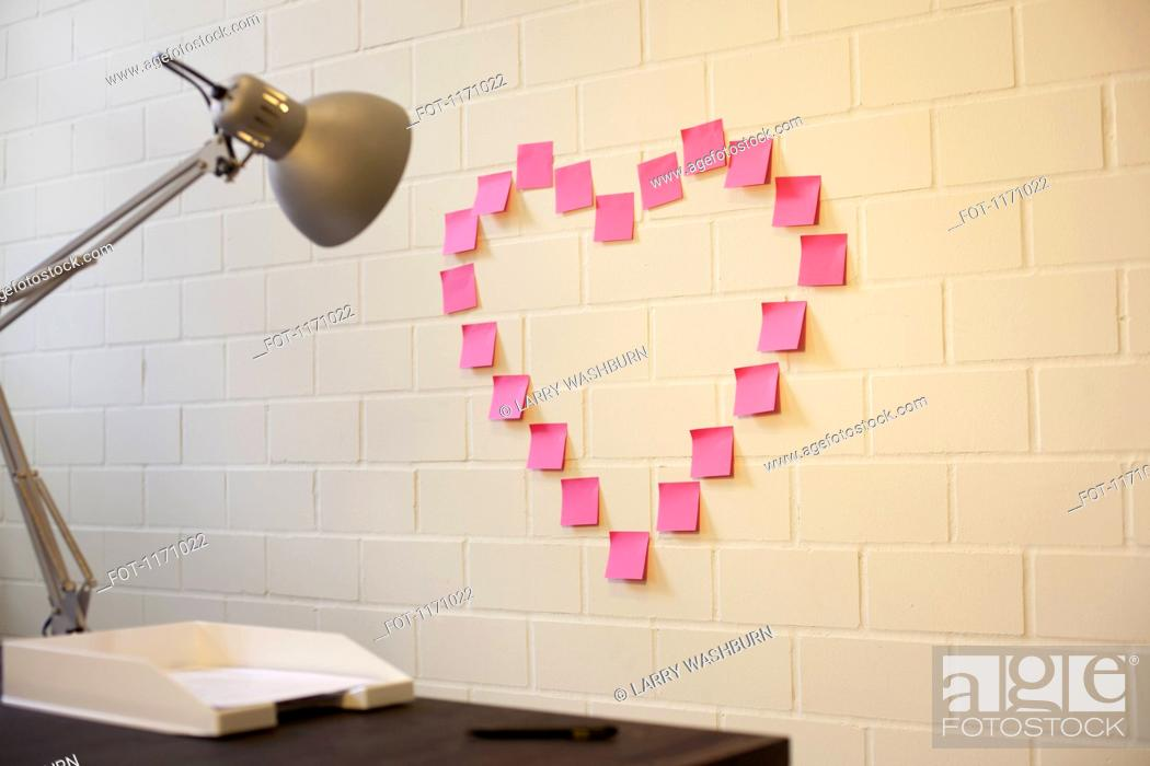 Stock Photo: Adhesive notes arranged into the shape of a heart on a wall next to a desk.