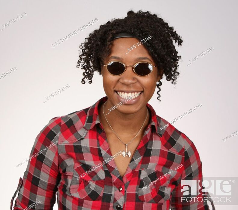 Stock Photo: Young African-American woman with sunglasses posing for portrait.