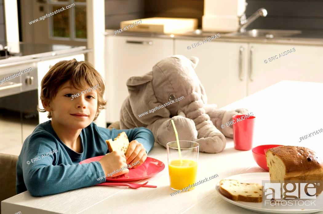 Stock Photo: Portrait of a boy having breakfast in the kitchen.