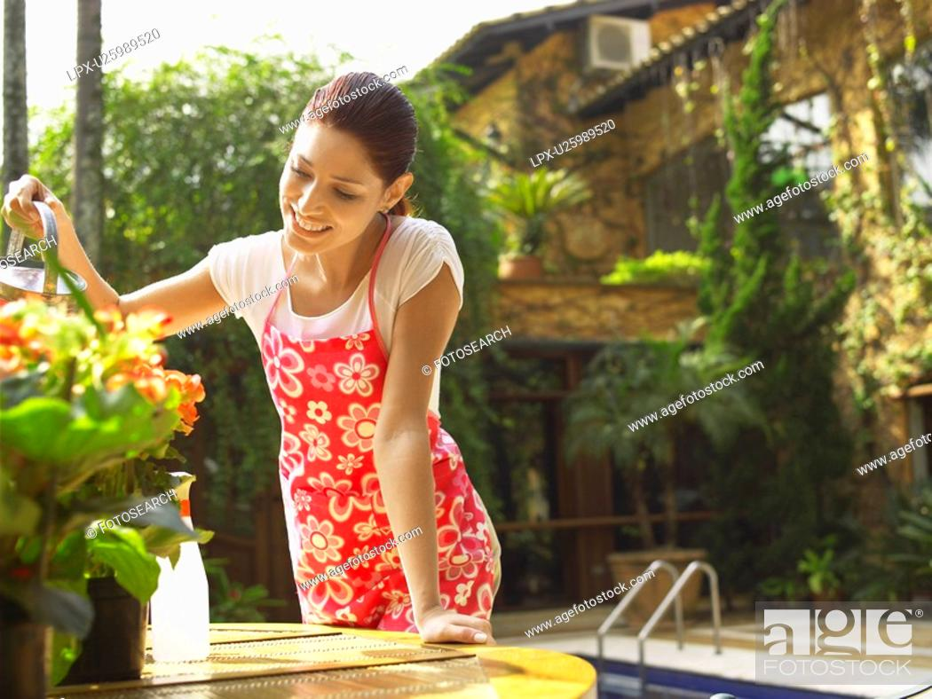 Stock Photo: Young woman watering flowers.