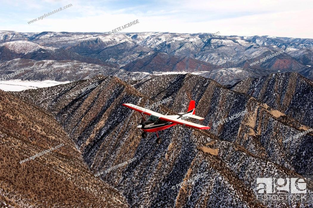 Stock Photo: A red and white plane flies over snow dusted Colorado mountains.