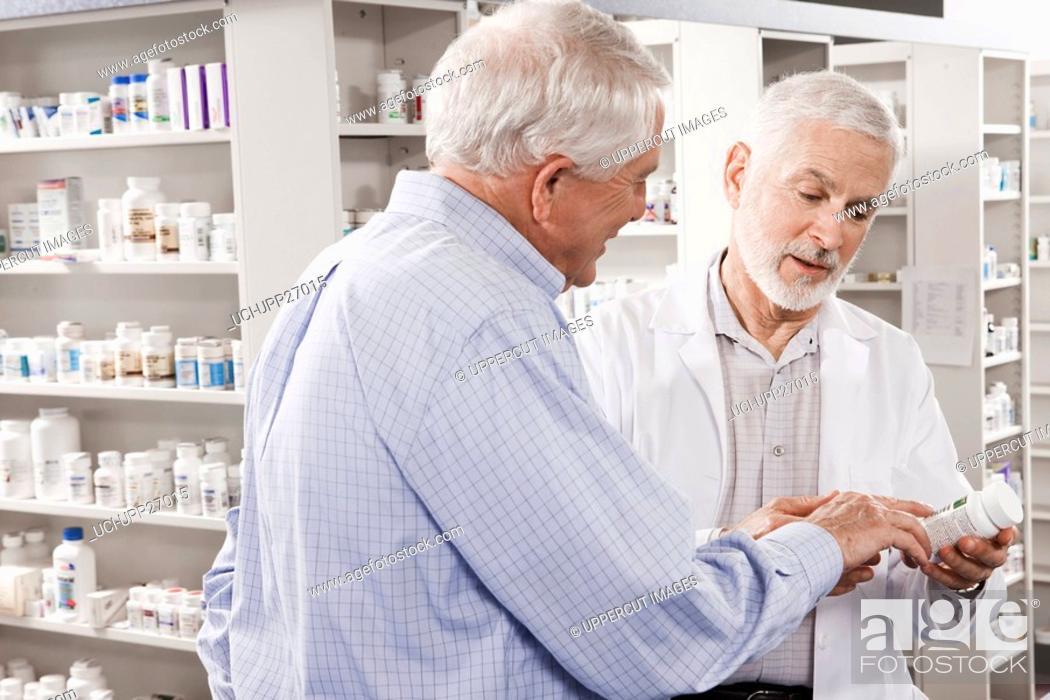 Stock Photo: Customer asking pharmacist about medication.